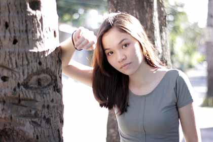 A photo of a beautiful Filipina leaning against a tree